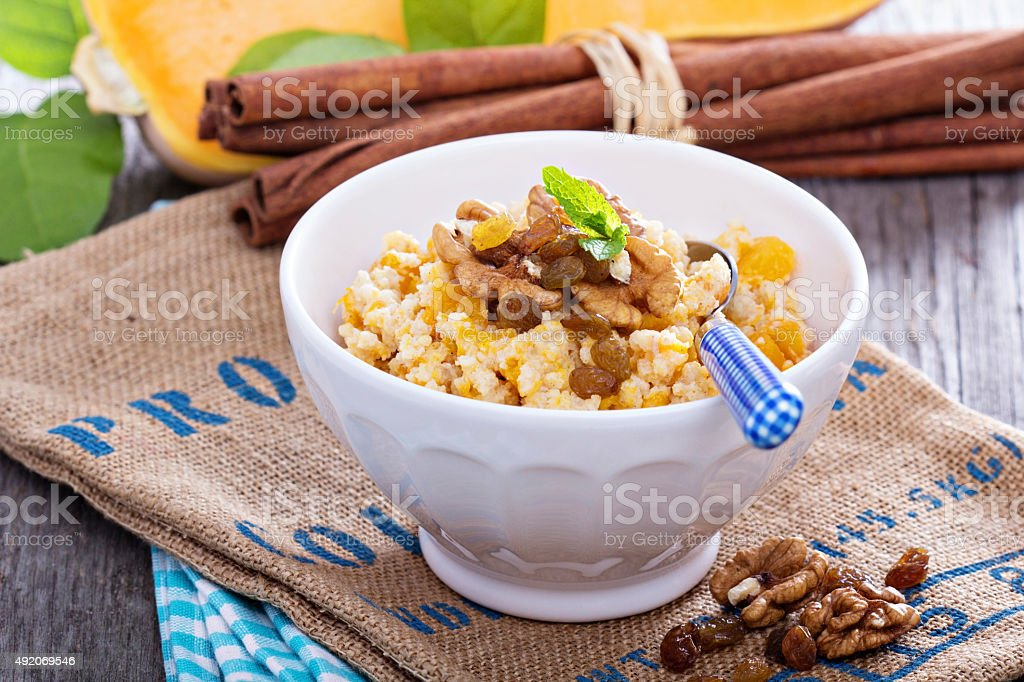 Pumpkin millet porridge with nuts and raisins stock photo
