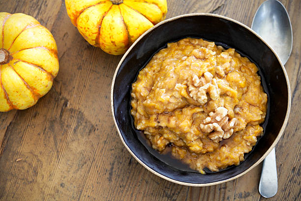 Pumpkin oatmeal Autumn morning pumpkin oatmeal with walnuts oatmeal stock pictures, royalty-free photos & images