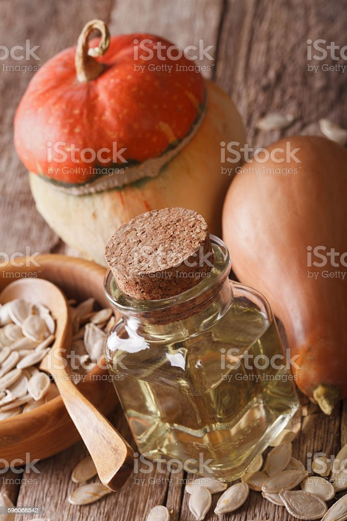 pumpkin oil close up with seeds on a table. vertical royalty-free stock photo