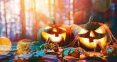 Happy Halloween! Pumpkins on wooden table on sunset sky background.