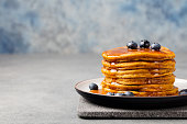 Pumpkin pancakes with maple syrup and blueberries on a plate.