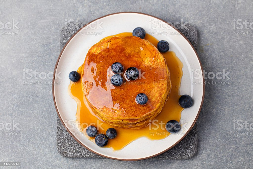 Pumpkin pancakes with maple syrup and blueberries. Top view stock photo