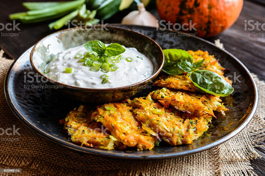 Pumpkin pancakes with zucchini and served with sour cream dip foto royalty-free