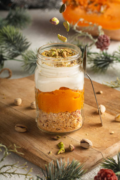Pumpkin parfait with pistachios in Glass Mason Jar Mugs on a wooden board against a background of New Year decorations, pistachios falling from above. stock photo