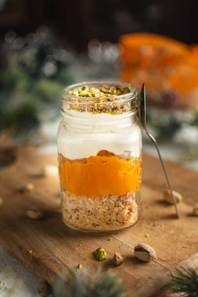 Pumpkin parfait with pistachios in Glass Mason Jar Mugs on a wooden board, a spoon, against a background of New Year decorations stock photo