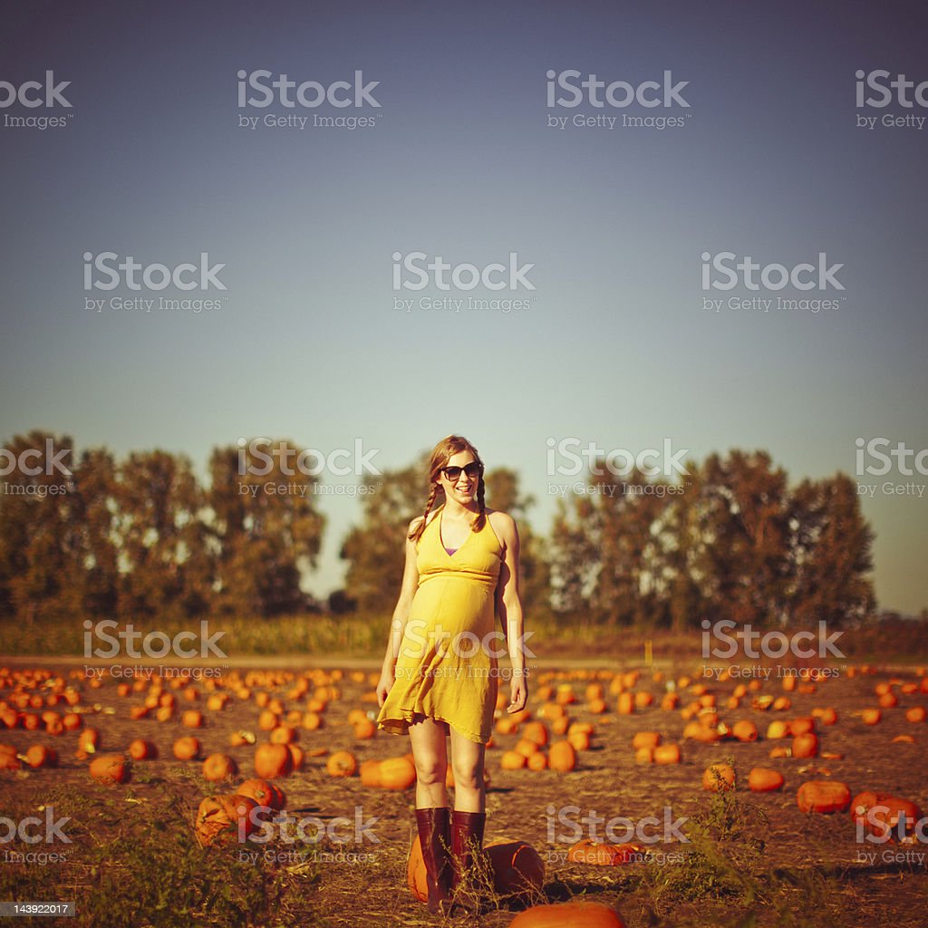 Pumpkin Patch with Cute Pregnant Woman in Vintage Tones royalty-free stock photo