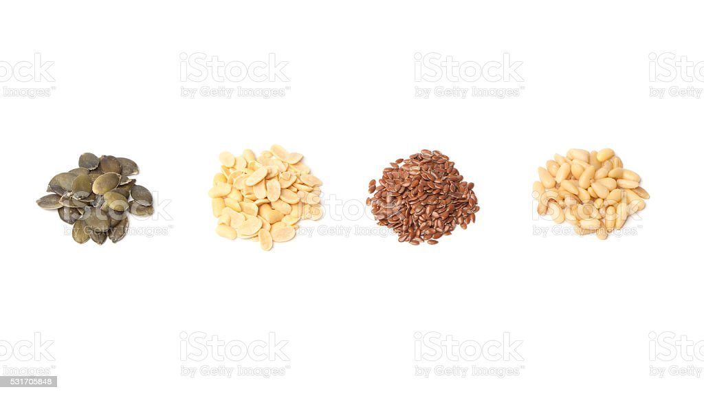 Pumpkin, peanut, linseed, pine seeds on white stock photo