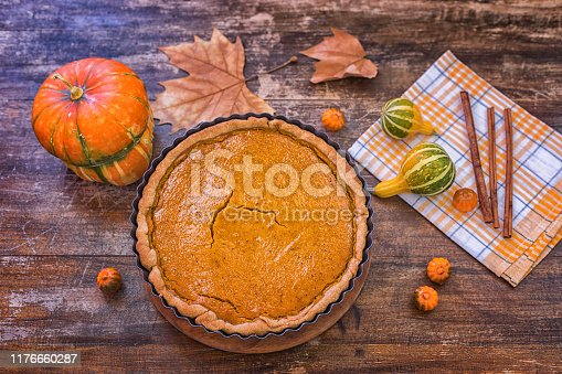 Fresh made pumpkin pie in pie mold at rustic table with decorative pumpkin, no people