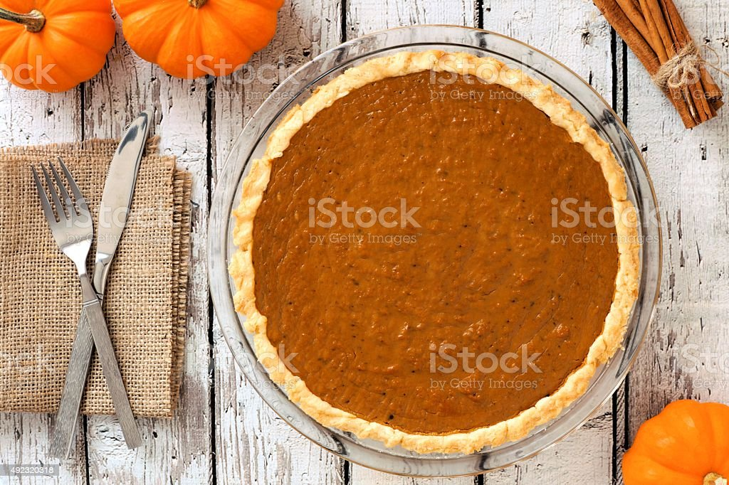 Pumpkin pie downward view on rustic white wood background stock photo