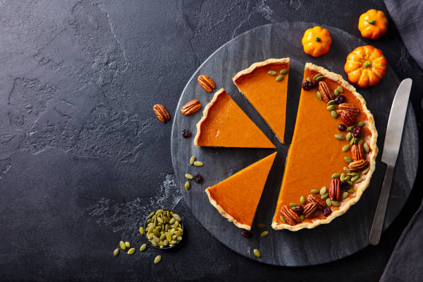 Pumpkin pie on marble cutting board. Dark background. Copy space. Top view. stock photo