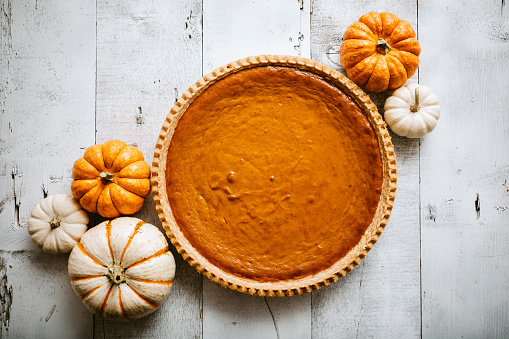 A high angle view looking down on a freshly baked pumpkin pie, just in time for your autumn or Thanksgiving season celebration.  Small decorative gourds decorate the scene.  Horizontal image with copy space.