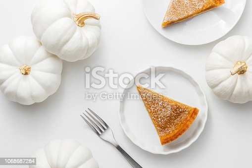 Pumpkin pie on a white plate with pumpkins on a white background, homemade autumn food for thanksgiving concept