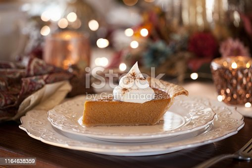 Thanksgiving holiday pumpkin pie with whipped topping.