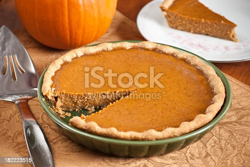 A pumpkin pie with a wedge cut out and sitting on a plate for serving.More homemade pies: