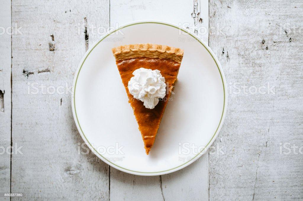Pumpkin Pie Slice on Rustic Background stock photo
