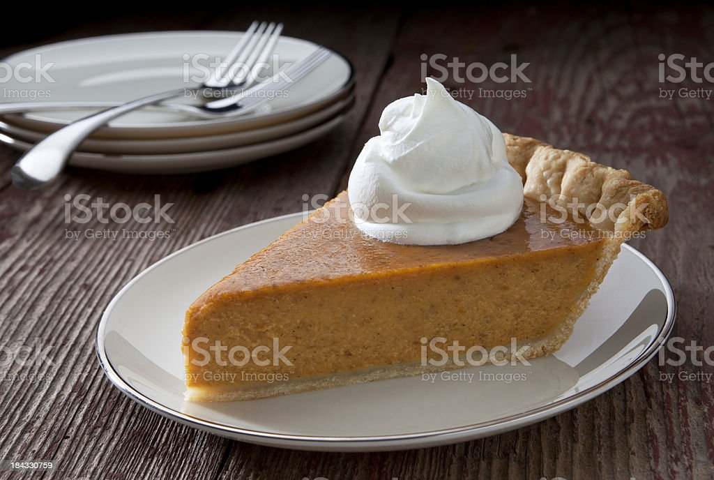 Pumpkin Pie slice with whipped cream on a rustic table. stock photo