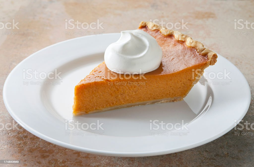 Pumpkin Pie Slice With Whipped Cream on Marble Table. stock photo