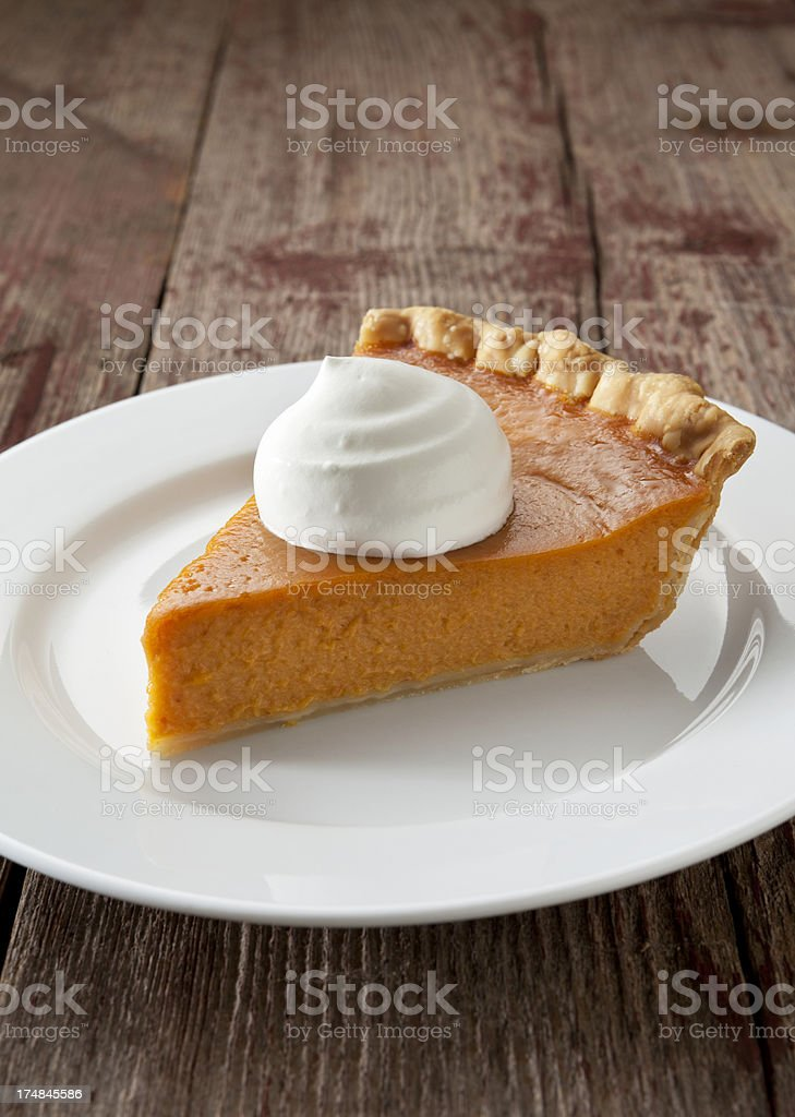 Pumpkin Pie Slice With Whipped Cream on Rustic Background. stock photo