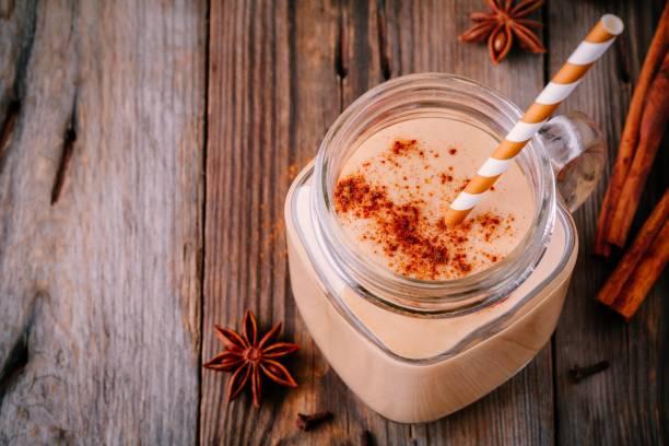 kürbiskuchen-smoothie mit zimt in einmachglas - einmachglassmoothie stock-fotos und bilder