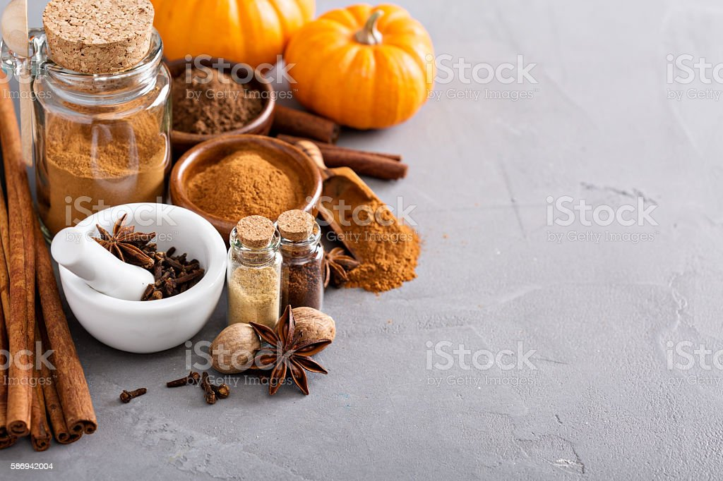 Pumpkin pie spice in a glass jar with ingredients stock photo