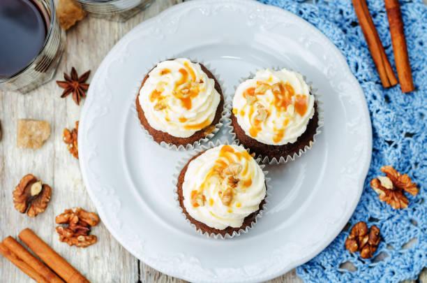 kürbiskuchen gewürze nüsse bananen cupcakes mit gesalzenem karamell und frischkäse frosting - heiße schokoladen cupcakes stock-fotos und bilder