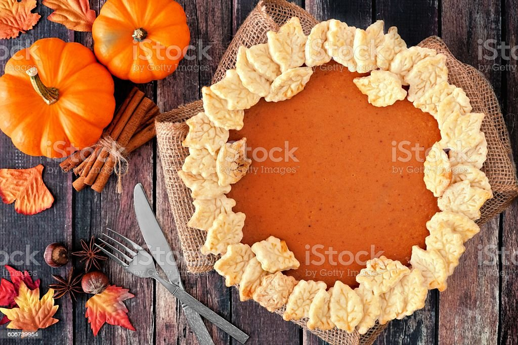 Pumpkin pie with autumn leaf pastry design, over rustic wood stock photo