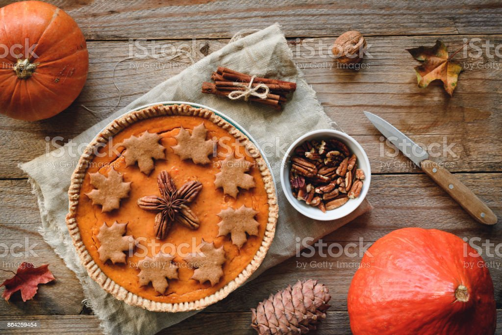 Pumpkin pie with pecan nuts on wooden background royalty-free stock photo