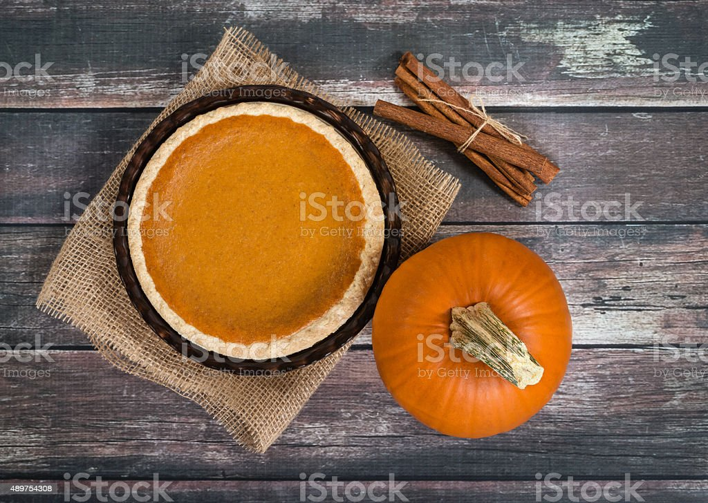 Pumpkin pie with pumpkin and cinnamon sticks against rustic table stock photo