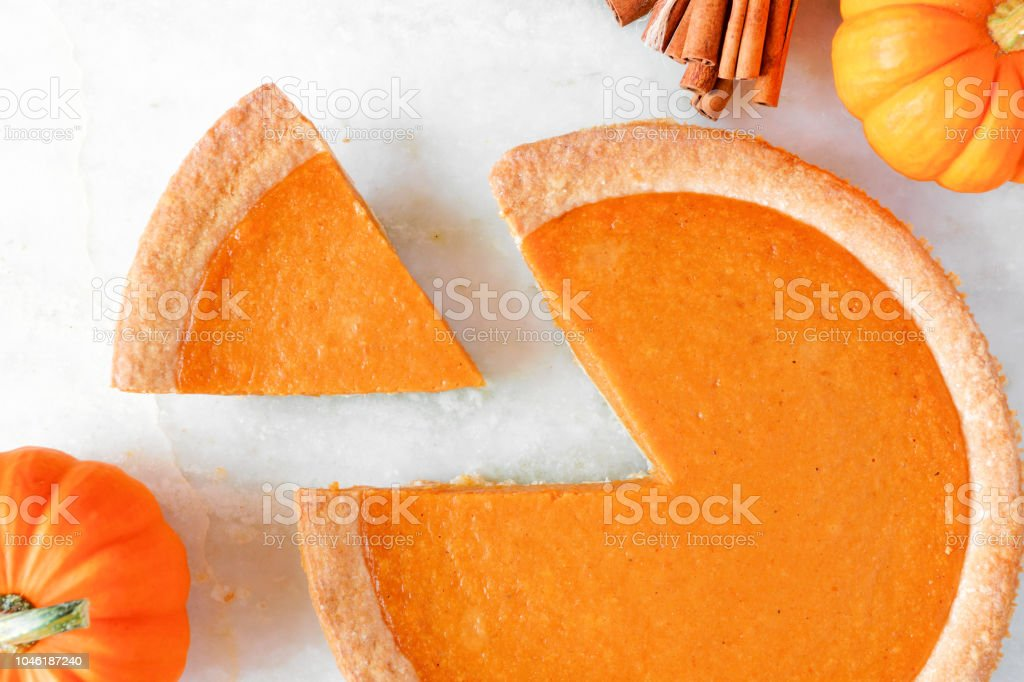 Pumpkin pie with slice removed, top view, close up stock photo