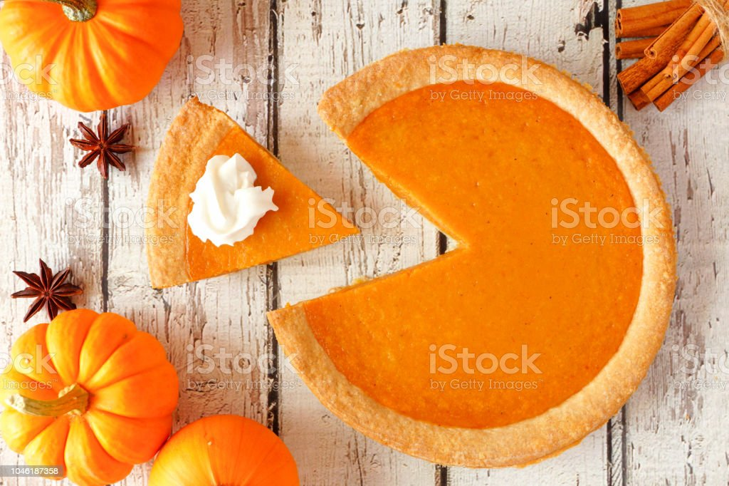 Pumpkin pie with slice removed, top view table scene on white wood stock photo