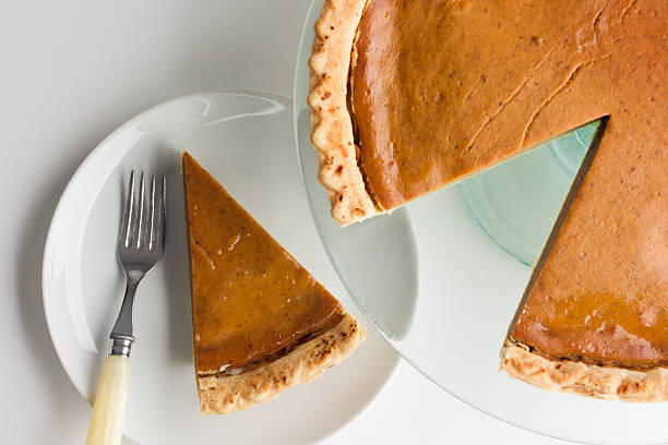 pumpkin pie with sliced piece on plate for thanksgiving dessert - pumpkin pie 個照片及圖片檔