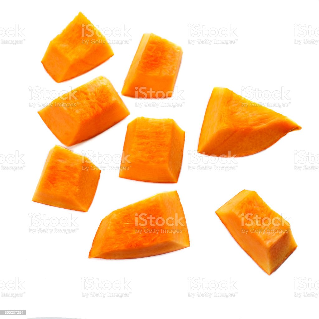 Pumpkin pieces cut in a  cube slice isolated on white background. Diced Pumpkin, close up. stock photo