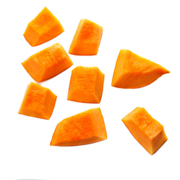 Pumpkin pieces cut in a  cube slice isolated on white background. Diced Pumpkin, close up. Pumpkin pieces cut in a  cube slice isolated on white background. Diced Pumpkin, close up. squash vegetable stock pictures, royalty-free photos & images