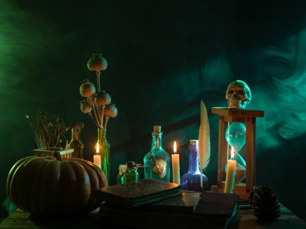 pumpkin, poison bottle, dead insects, candles, human skull and magic book for halloween - традиционная церемония стоковые фото и изображения
