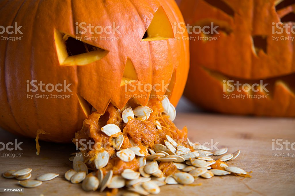 Pumpkin puking with pumpkin seeds on wood table stock photo