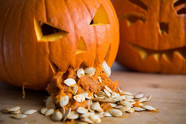 pumpkin puking with pumpkin seeds on wood table - kotze stock-fotos und bilder