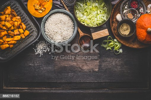 istock Pumpkin risotto cooking ingredients on dark rustic kitchen table with bowls, spoon and pan 888216152