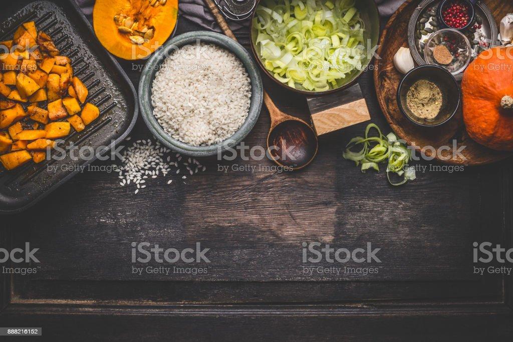 Risoto de abóbora cozinhar ingredientes na mesa de cozinha rústica escura com taças, colher e pan - foto de acervo