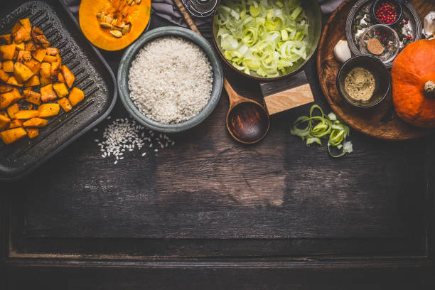pompoen risotto ingrediënten op donkere rustieke keukentafel met kommen, lepel en pan koken - pan keukengereedschap stockfoto's en -beelden