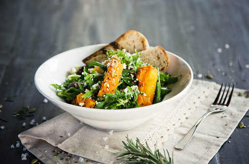 Rocket salad with baked pumpkin, feta cheese, seeds and bread