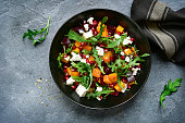 Pumpkin salad with beetroot, arugula and feta cheese in a black bowl over dark grey slate, stone or concrete background.Top view.