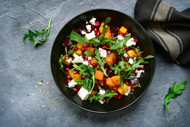 Pumpkin salad with beetroot, arugula and feta cheese Pumpkin salad with beetroot, arugula and feta cheese in a black bowl over dark grey slate, stone or concrete background.Top view. beet stock pictures, royalty-free photos & images