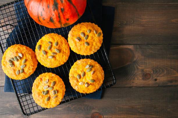 kürbis scones auf einem kuchengitter über hölzerne hintergrund. - scones backen stock-fotos und bilder