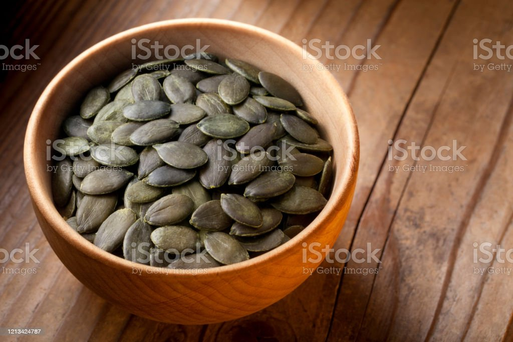 Pumpkin seeds in wooden bowl Pumpkin seeds in wooden bowl. Agriculture Stock Photo
