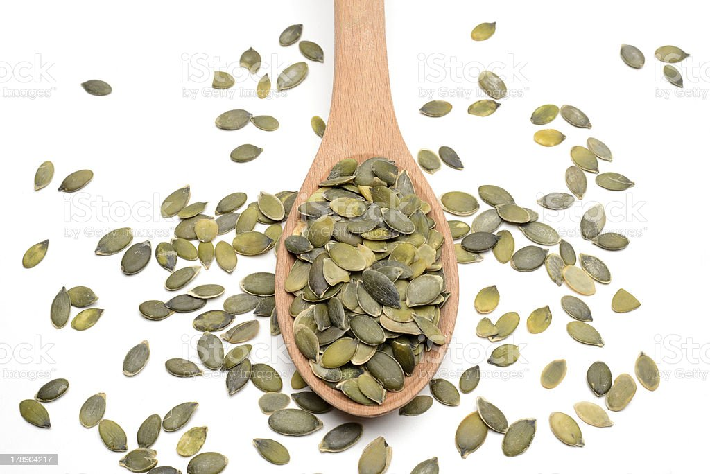 Pumpkin seeds on wood spoon stock photo
