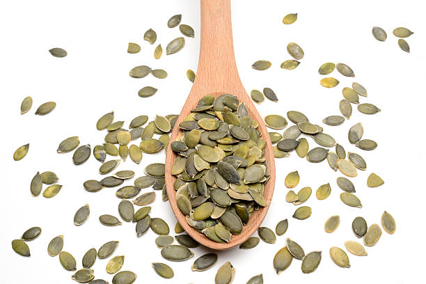 Pumpkin seeds on wood spoon stock photo