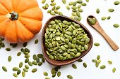 Pumpkin seeds in a wooden bowl on a white table