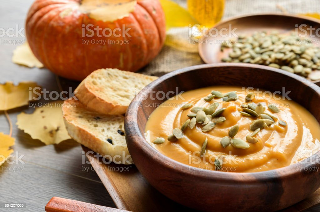 Pumpkin soup in a wooden bowl, with autumn leaves and pumpkin royalty-free stock photo