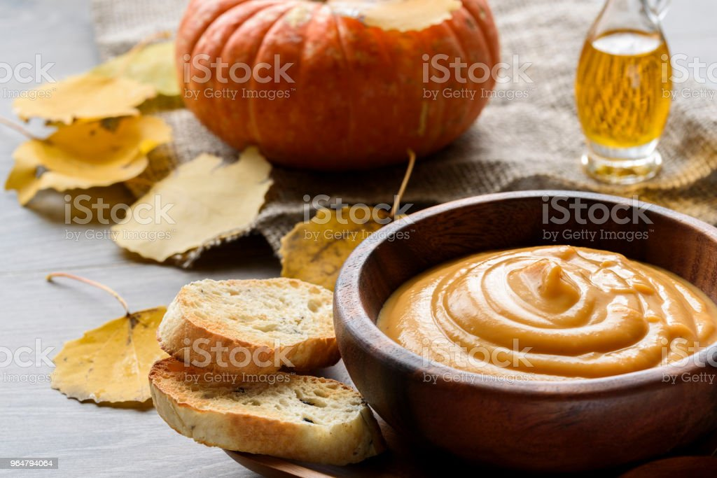Pumpkin soup in a wooden bowl, with autumn leaves and pumpkin. royalty-free stock photo