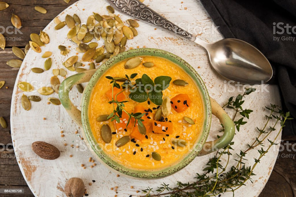 Pumpkin soup in beige bowl with pieces of pumpkin, seeds and herbs on old wooden background. royalty-free stock photo